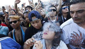 In this April, 2014 photo, partygoers listen to live music and smoke pot at the annual 4/20 marijuana festival in Denver, Colorado. (AP Photo/Brennan Linsley, File)