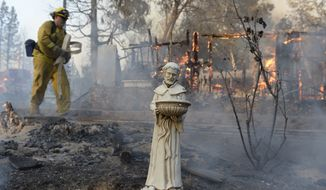 A religious statue is almost all that is left from a home that burned to the ground on Cedar Dr. in Oakhurst,  Calif., Sunday, Sept. 14, 2014. (AP Photo/The Fresno Bee, Mark Crosse)