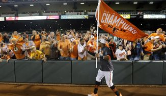 Baltimore Orioles center fielder Adam Jones greets fans after a baseball game against the Toronto Blue Jays, Tuesday, Sept. 16, 2014, in Baltimore. Baltimore won 8-2 to clinch the American League East. (AP Photo/Patrick Semansky)