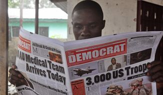 In Monrovia, Liberia, a man reads a newspaper headlining President Barack Obama's plan to send 3,000 U.S. troops to West Africa to help contain the deadly Ebola virus. (AP Photo/Abbas Dulleh)
