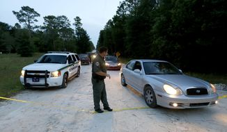 A Gilchrist County sheriff's deputy lowers the yellow tape to let vehicles through at the scene of a shooting on Thursday, Sept. 18, 2014 in Bell, Fla. Officials said two adults and six children are dead in the incident. (AP Photo/The Gainesville Sun, Matt Stamey)