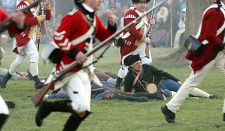 In a reenactment of the Battle of Lexington, the beginning of the American Revolution, British soldiers are called back by their officers, as they run back to their lines and past the dead and wounded, Monday, April 21, 2014, in Lexington, Mass. (AP Photo/The Metro West Daily News, Ann Ringwood)