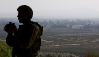 In this Monday, Sept. 1, 2014, file photo, an Israeli soldier observes Syria's Quneitra province at an observation point on Mount Bental in the Israeli-controlled Golan Heights, overlooking the border with Syria. (AP Photo/Sebastian Scheiner, File)