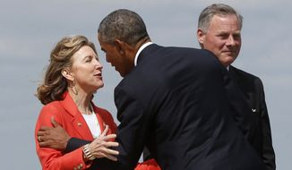 FILE - In this Aug. 26, 2014 file photo, President Barack Obama is greeted by Sen. Kay Hagan, D-N.C., left, as he arrives at North Carolina Air National Guard Base in Charlotte, N.C.  Obama was in Charlotte to address the American Legion's 96th National Convention. At right is Sen. Richard Burr, R-N.C.   Republicans are asking voters to judge Hagan as too closely aligned with the president.  (AP Photo/Charles Dharapak)