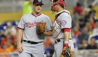 Washington Nationals starting pitcher Jordan Zimmermann, left,  confers with catcher Wilson Ramos in the first inning against the Miami Marlins during a baseball game in Miami, Saturday, Sept. 20, 2014. (AP Photo/Joe Skipper)