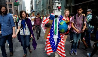 """Elliot Crown of New York parades in a costume called """"Fossil Fool."""" The goal of signing a climate deal could better be facilitated more by strategic negotiations rather than distracting protest marches. (Associated Press)"""