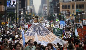 People fill the street during the People's Climate March, Sunday, Sept. 21, 2014, in New York. Tens of thousands of activists walked through Manhattan on Sunday, warning that climate change is destroying the Earth — in stride with demonstrators around the world who urged policymakers to take quick action. (AP Photo/Mel Evans)