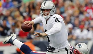 New England Patriots defensive end Rob Ninkovich (50) tries to take down Oakland Raiders quarterback Derek Carr (4) in the first half of an NFL football game, Sunday, Sept. 21, 2014, in Foxborough, Mass. (AP Photo/Elise Amendola)