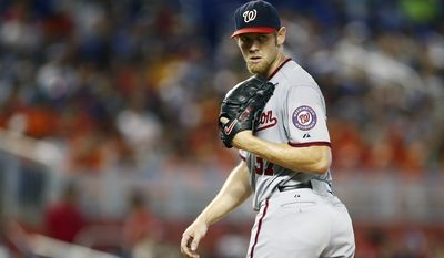 Washington Nationals starter Stephen Strasburg checks Miami Marlins runner Donovan Solano at first during the first inning of a baseball game in Miami, Sunday, Sept. 21, 2014. (AP Photo/J Pat Carter)