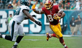 Washington Redskins' Niles Paul, right, tries to break past Philadelphia Eagles' Trent Cole (58) during the first half of an NFL football game, Sunday, Sept. 21, 2014, in Philadelphia. (AP Photo/Matt Rourke)