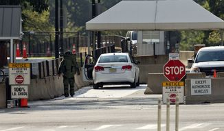 An explosive technician in a bomb suit approaches a vehicle near the entrance to White House in Washington, Saturday. The Secret Service says two men were arrested in separate recent incidents for trying to unlawfully enter the White House. (AP Photo/Pablo Martinez Monsivais)