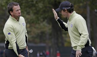 Europe's Graeme McDowell, left, is congratulated by Rory McIlroy after making a putt to half the 13th hole during a foursomes match at the Ryder Cup PGA golf tournament Friday, Sept. 28, 2012, at the Medinah Country Club in Medinah, Ill. (AP Photo/David J. Phillip)