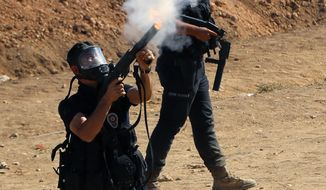 Riot police use teargas to disperse Kurdish demonstrators who were clashing with Turkish security forces as thousands of Syrian refugees continue to arrive at the border in Suruc, Turkey, Monday, Sept. 22, 2014. Turkey opened its border Saturday to allow in up to 60,000 people who massed on the Turkey-Syria border, fleeing the Islamic militants' advance on Kobani.(AP Photo/Burhan Ozbilici)
