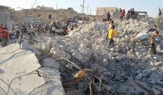 aftermath: Syrians sift through the rubble of a house targeted by coalition airstrikes in the village of Kfar Derian. Washington informed President Bashar Assad's government of imminent U.S. strikes against Islamic State group strongholds hours before the bombing began. (Associated Press)