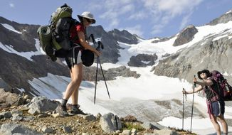 FILE - In this August 2013 file photo, Holly Weiler, left, and Samantha Journot of the Spokane Mountaineers hike past Lyman Glacier as they head toward Spider Gap to complete a loop backpacking trek in Washington state's Glacier Peak Wilderness. The U.S. Forest Service is proposing rules that restrict filming and photography by media organizations and others in more than 100 million acres of the nation's wilderness, Wednesday, Sept. 24, 2014.  (AP Photo/The Spokesman-Review, Rich Landers, File) COEUR D'ALENE PRESS OUT