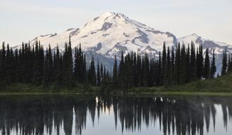 FILE - This August 2013 file photo shows Glacier Peak, elevation 10,541 feet, behind Image Lake in Washington state's Glacier Peak Wilderness. The U.S. Forest Service is proposing rules that restrict filming and photography by media organizations and others in more than 100 million acres of the nation's wilderness, Wednesday, Sept. 24, 2014.  (AP Photo/The Spokesman-Review, Rich Landers, File) COEUR D'ALENE PRESS OUT