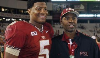 Florida State quarterback Jameis Winston (5) poses with former Florida State quarterback and Heisman Trophy winner Charlie Ward after an NCAA college football game against Syracuse on Saturday, Nov. 16, 2013, in Tallahassee, Fla. Florida State best Syracuse 59-3. (AP Photo/Phil Sears)