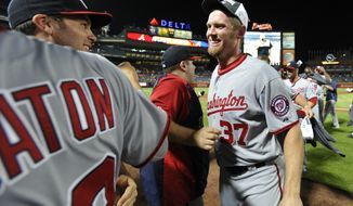 Washington Nationals pitcher Stephen Strasburg (37) celebrates with his team after clinching the NL East division against the Atlanta Braves in a baseball game Tuesday, Sept. 16, 2014, in Atlanta. Washington won 3-0. (AP Photo/David Tulis)