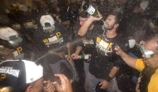 Pittsburgh Pirates shortstop Chase d'Arnaud raises a bottle as he and teammates celebrate in the locker room after defeating the Atlanta Braves 3-2 in a baseball game to clinch a playoff berth, Tuesday, Sept. 23, 2014, in Atlanta. (AP Photo/John Bazemore)