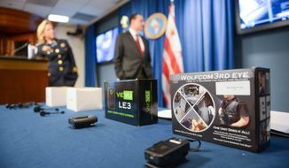 D.C. police Chief Cathy Lanier (left) and Mayor Vincent Gray announce that the police department is testing five different kinds of body-worn cameras as part of a pilot program during a press conference at the Wilson Building in D.C. on Sept. 24, 2014. (Andrew Harnik/The Washington Times) **FILE**