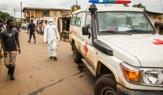 A health worker, left, is seen on his way to collect a man suspected of suffering from the Ebola virus, in Freetown, Sierra Leone, Wednesday, Sept. 24, 2014. U.S. health officials Tuesday laid out worst-case and best-case scenarios for the Ebola epidemic in West Africa, warning that the number of infected people could explode to at least 1.4 million by mid-January — or peak well below that, if efforts to control the outbreak are ramped up.(AP Photo/ Michael Duff)