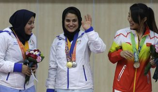In this Monday, Sept. 22, 2014 file photo, gold medalist Najmeh Khedmati of Iran, center, waves to photographers as silver medalist and her compatriot Narjes Emamgholinejad Andevari, left, and bronze medalist Zhang Binbin of China smile at her during the victory ceremony for the women's 10m air rifle shooting competition at the 17th Asian Games at Ongnyeon International Shooting Range in Incheon, South Korea. The Qatar women's basketball team forfeited its Asian Games match against Mongolia after players were refused permission to wear a hijab. (AP Photo/Dita Alangkara, File)