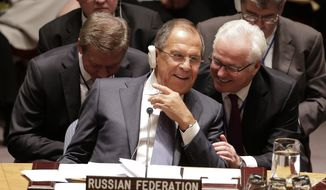 Russian Foreign Minister Sergey Lavrov, left, speaks with Ambassador Vitaly Churkin during a UN Security Council meeting, Wednesday, Sept. 24, 2014, at the United Nations. Members of the Security Council were expected to adopt a resolution that would require all countries to prevent the recruitment and transport of would-be foreign fighters preparing to join terrorist groups such as the Islamic State group. (AP Photo/Julie Jacobson)