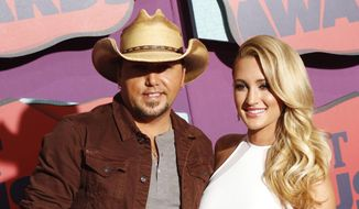 "FILE - In this June 4, 2014 file photo, country singer Jason Aldean, left, and Brittany Kerr arrive at the CMT Music Awards in Nashville, Tenn. Aldean and former ""American Idol"" contestant Brittany Kerr are engaged to be married. A publicist for Aldean confirmed on Thursday, Sept. 25, that the couple had gotten engaged, which was first reported by TMZ. Aldean filed for divorce from his wife, Jessica, last year after pictures surfaced of him and Kerr in Los Angeles bar. (Photo by Wade Payne/Invision/AP, File)"