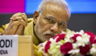Indian Prime Minister Narendra Modi sits during the launche his 'Make in India' initiative, prior to his scheduled departure to the U.S.  in New Delhi, India, Thursday, Sept. 25, 2014. Modi's five-day trip starting Friday is tightly packed: He will be meeting Obama and a slew of top American officials, addressing the U.N. General Assembly, interacting with the heads of major U.S. companies and influential Indian-Americans. (AP Photo/Saurabh Das)
