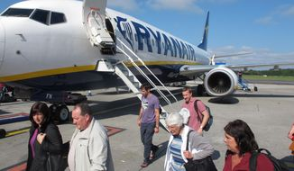 In this photo taken on Sept. 21, 2014, passengers exit a Ryanair flight at Dublin Airport.  Ryanair says it plans to carry an extra 1 million passengers this year and has raised its profits outlook on the back of wide-ranging service improvements that have boosted sales and filled more aircraft. The Dublin-based carrier told its annual general meeting Thursday that it plans to carry 87 million passengers in this fiscal year, better than its previous forecast of 86 million, and record net profits at or close to 650 million euros ($825 million), the top of its previously guided range. (AP Photo/Shawn Pogatchnik)