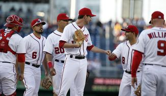 Washington Nationals relief pitcher Jerry Blevins (13) fist bumps second baseman Danny Espinosa (8) as manager Matt Williams (9) walks out to relieve him during a baseball game against the Miami Marlins at Nationals Park Thursday, April 10, 2014, in Washington. The Nationals won 7-1. (AP Photo/Alex Brandon)