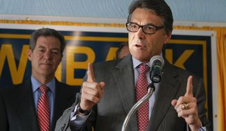 Texas Gov. Rick Perry stumps for Kansas Gov. Sam Brownback, left, during a campaign rally for Brownback on Wednesday, Sept. 24, 2014 in Wichita, Kan. Brownback is facing a tough reelection campaign against democrat Paul Davis. (AP Photo/The Wichita Eagle, Travis Heying)
