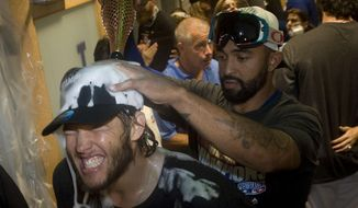 The Dodgers' Clayton Kershaw has champagne poured over his head my Matt Kemp after the Dodgers clinched the National League West against the San Francisco Giants at Dodger Stadium Wednesday nightSept. 24, 2014. The Los Angeles Dodgers won the NL West title with a 9-1 victory over the second-place San Francisco Giants on Wednesday night. (AP Photo/The Orange County Register, Kevin Sullivan)