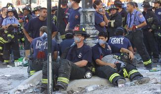 Firefighters rest as rescue efforts continue at the World Trade Center in New York Wednesday Sept. 12, 2001. (Associated Press)