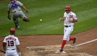 Washington Nationals' Ryan Zimmerman, right, scores as New York Mets catcher Juan Centeno, left, chases the ball during the fourth inning of the first baseball game of a double-header, Thursday, Sept. 25, 2014, in Washington. Also seen is Washington Nationals' Kevin Frandsen. (AP Photo/Nick Wass)