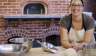 ADVANCE FOR SUNDAY, SEPT. 28, 2014 AND THEREAFTER -- In this Tuesday, Sept. 16, 2014 photo food historian and artisan baker Tani Mauriello stands with baking materials in the new Artisan Craft Center, at the Plimoth Plantation museum, in Plymouth, Mass. The bakery, where visitors will be able to get a taste of 17th-century living, was added during the renovation of the museum's Craft Center inside the former Hornblower Carriage House. (AP Photo/Cape Cod Times/Christine Hochkeppel) MANDATORY CREDIT