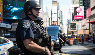 A New York City cop stands watch in Times Square. (Associated Press) ** FILE **