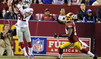 New York Giants wide receiver Rueben Randle (82) hauls in a first down in front of Washington Redskins cornerback David Amerson (39) in the third quarter at FedExField, Landover, Md., Sept. 25, 2014. (Preston Keres/Special for The Washington Times)