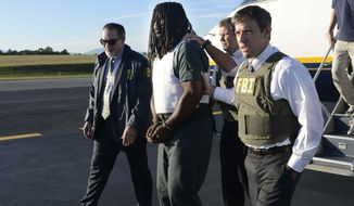 In this Friday, Sept. 26, 2014 photo provided by the FBI, agents escort Jesse Leroy Matthew, Jr., center, from a plane during extradition to Charlottesville, Va. Matthew, 32, is suspect in the Sept. 13, 2014 disappearance of University of Virginia student Hannah Graham. (AP Photo/FBI)