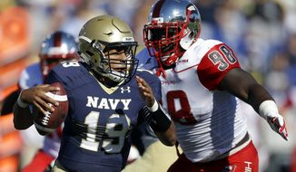 Navy quarterback Keenan Reynolds, left, looks for a receiver as he is tackled by Western Kentucky defensive lineman Devante Terrell in the first half of an NCAA college football game in Annapolis, Md., Saturday, Sept. 27, 2014. (AP Photo/Patrick Semansky)