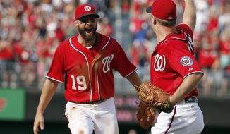 Washington Nationals third baseman Kevin Frandsen (19) comes to celebrate with starting pitcher Jordan Zimmermann (27) after a baseball game against the Miami Marlins at Nationals Park, Sunday, Sept. 28, 2014, in Washington. Zimmermann pitched a no-hitter as the Nationals won 1-0.(AP Photo/Alex Brandon)