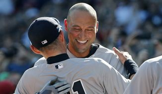 New York Yankees designated hitter Derek Jeter hugs teammate Ichiro Suzuki after coming out of the baseball game for a pinch-runner in the third inning against the Boston Red Sox in a baseball game at Fenway Park, Sunday, Sept. 28, 2014, in Boston. It is the last baseball game of Jeter's career. (AP Photo/Elise Amendola)