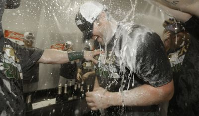 Oakland Athletics designated hitter Adam Dunn is sprayed by his teammates in the locker room  after winning the baseball game against the Texas Rangers 4-0 clinching a playoff spot Sunday, Sept. 28, 2014,  in Arlington, Texas. (AP Photo/LM Otero)