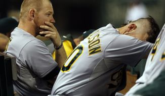 Oakland Athletics first baseman Brandon Moss, left, and third baseman Josh Donaldson, right, witnaess a scoring opportunity slip away during the eighth inning of a baseball game against the Texas Rangers, Saturday, Sept. 27, 2014, in Arlington, Texas. The Rangers won 5-4.  (AP Photo/John F. Rhodes)