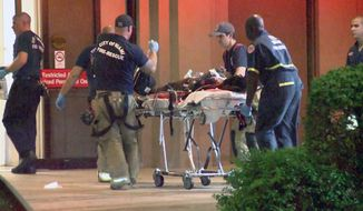 In this image taken from video, emergency personnel wheel a person wounded in a shooting at The Spot, a nightclub in Miami, early Sunday, Sept. 28, 2014. Fifteen people were wounded in the early morning shooting, including an 11-year-old, police said.  (AP Photo/APTN)
