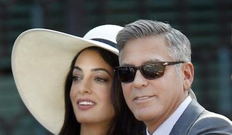 George Clooney, right, flanked by his wife Amal Alamuddin, arrives at the Cavalli Palace for the civil marriage ceremony in Venice, Italy, Monday, Sept. 29, 2014. George Clooney married human rights lawyer Amal Alamuddin Saturday, the actor's representative said, out of sight of pursuing paparazzi and adoring crowds. (AP Photo/Luca Bruno) ** FILE **