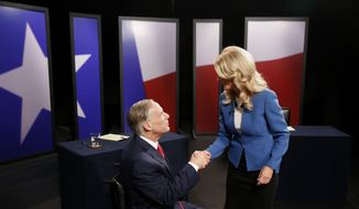 Texas State Senator Wendy Davis, right, Democratic Gubernatorial candidate, and Texas Attorney General Greg Abbott, left, Republican Gubernatorial candidate, shake hands before the final gubernatorial debate in a KERA-TV studio in Dallas on Tuesday Sept. 30, 2014. (AP Photo/The Dallas Morning News, Andy Jacobsohn, Pool)