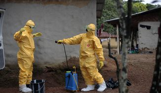 Gordon Kamara, left, is sprayed by Konah Deno after they loaded six patients suspected to have been infected by the Ebola virus into their ambulance in the village of Freeman Reserve, about 30 miles north of Monrovia, Liberia, Tuesday, Sept. 30, 2014. (AP Photo/Jerome Delay)