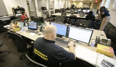 Dallas Emergency Management specialist Greg Guthrie works with others branches of government offices in the Office of Emergency Management, Wednesday, Oct. 1, 2014, in Dallas. Dallas Mayor Mike Rawlings has activated a city emergency management center after a patient was confirmed with the first case of Ebola diagnosed in the U.S. (AP Photo/Tony Gutierrez)
