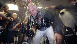 Members of the Baltimore Orioles pour beer and champagne on manager Buck Showalter after a baseball game against the Toronto Blue Jays, Tuesday, Sept. 16, 2014, in Baltimore. Baltimore won 8-2 to clinch the American League East. (AP Photo/Patrick Semansky)